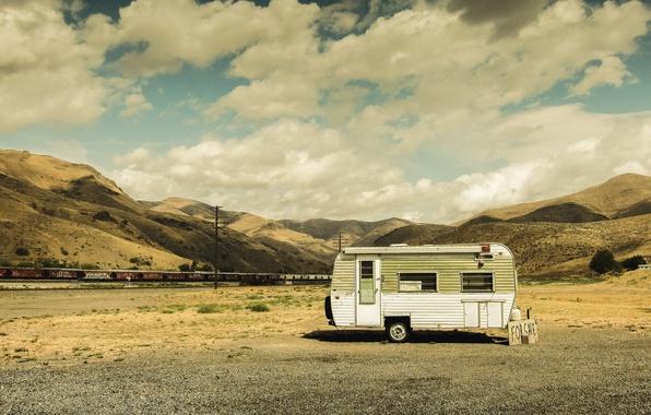 Picture the sky, clouds, hills, train, railroad, shadows, caravan, power lines, desert, selling, travel trailer