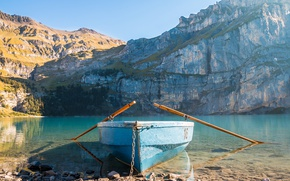Picture the sun, mountains, lake, stones, rocks, shore, boat, chain, paddles