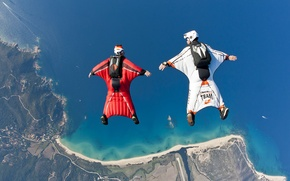 Picture the sky, water, the ocean, shore, mountain, skydivers, skydivers