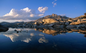 Picture the sky, clouds, sunset, mountains, lake, reflection, stones, rocks