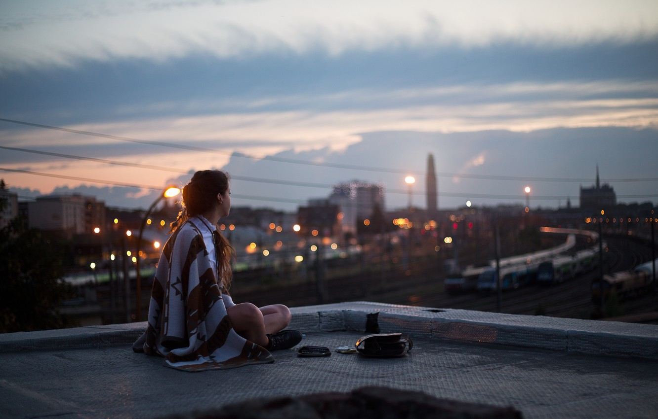 Photo wallpaper roof, girl, the city, lights, street, the evening, lights, blanket, plaid, sitting, looks